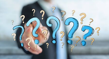 Businessman on blurred background touching hand drawn question marks with his fingers Stock Photo