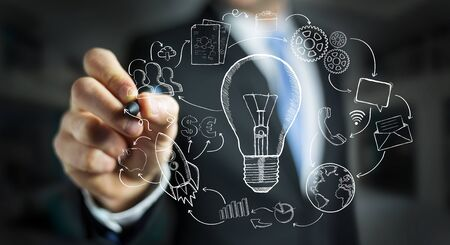 lamp light: Businessman drawing a lightbulb with a pen with multimedia icons flying around
