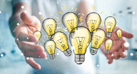 Businessman on blurred background holding hand-drawn lightbulb in his hand