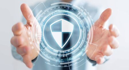 secure: Businessman on blurred background using shield safe protection to protect his datas 3D rendering