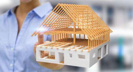 Donna di affari su fondo vago che tocca 3D che rende la casa non finita di piano con il suo dito