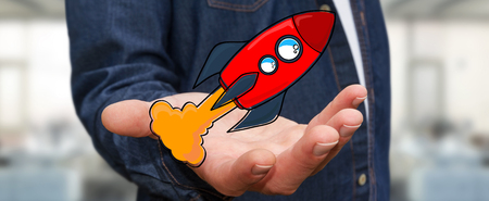 idea: Businessman on blurred background holding red hand drawn rocket in his hand