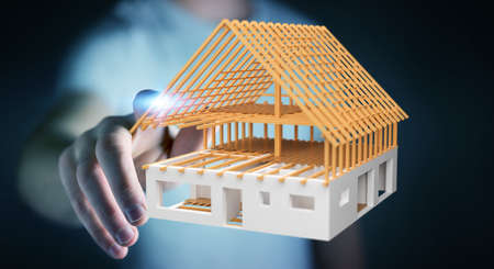 Businessman on blurred background touching 3D rendering unfinished plan house with his finger Stock Photo