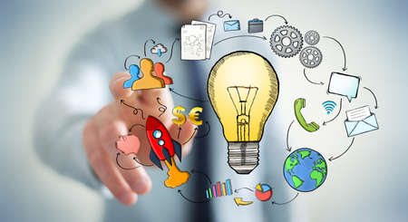 solution: Businessman touching hand drawn lightbulb with his fingers with multimedia icons flying around