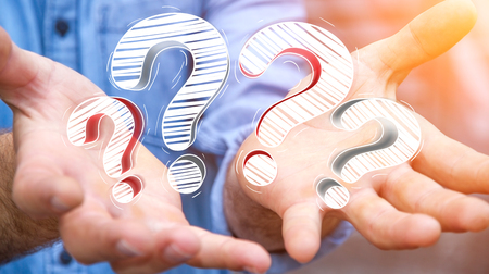 answer: Businessman on blurred background holding hand drawn question marks in his hand Stock Photo