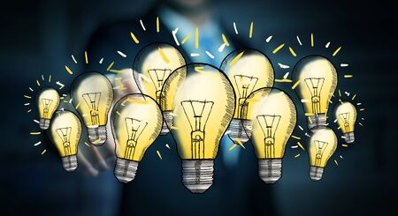 lamp light: Businessman on blurred background touching hand-drawn lightbulb with his finger