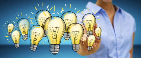solution: Businesswoman on blurred background touching hand-drawn lightbulb with her finger Stock Photo