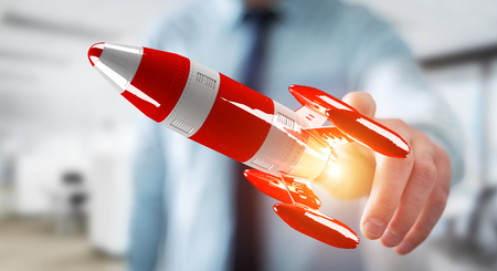 Businessman on blurred background holding red rocket in his hand 3D rendering Stock Photo