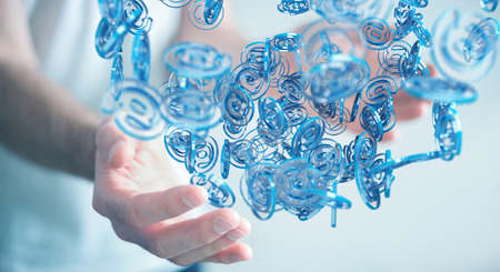 Businessman on blurred background using digital arobase blue sphere to surf on internet 3D rendering