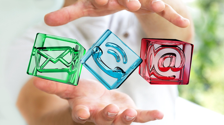 fingers: Businessman on blurred background holding transparent cube contact icon in his hand 3D rendering
