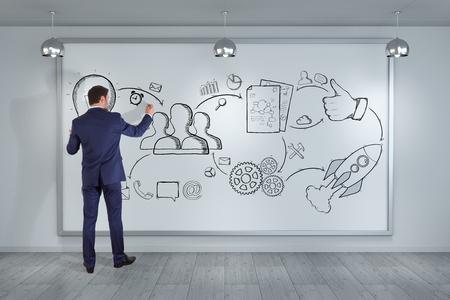 Hombre de negocios en interior moderno que dibuja un bosquejo del proyecto en una representación de la tarjeta 3D Foto de archivo