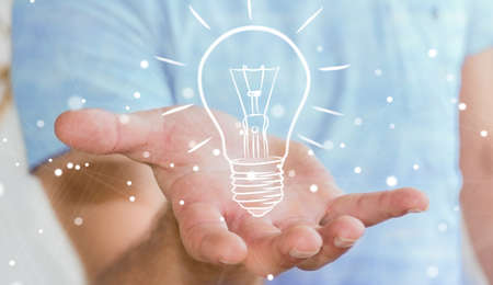fingers: Businessman on blurred background holding a sketch lightbulb Stock Photo