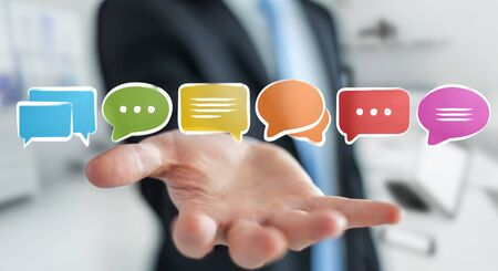 Businessman on blurred background holding discussion icons sketch Reklamní fotografie