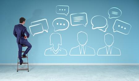 Uomo d'affari in interni moderni che guardano icone di discussione schizzo su un muro Rendering 3D