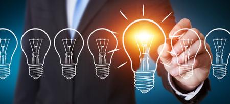 Uomo d'affari su sfondo sfocato disegno di un abbozzo lampadina con una penna