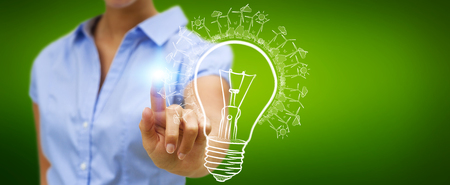 Businessmwoan on blurred background touching renewable eco lightbulb sketch