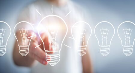 Businessman on blurred background touching a sketch lightbulb Imagens