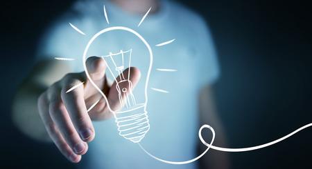 Businessman on blurred background touching a sketch lightbulb Standard-Bild