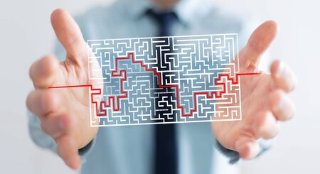 Businessman on blurred background searching solution of a complicated maze Stock Photo