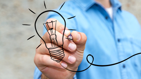 lamp light: Businessman on blurred background drawing a sketch lightbulb with a pen