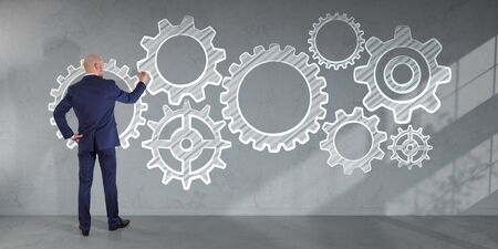 Businessman in modern interior drawing gears sketch on a wall 3D rendering