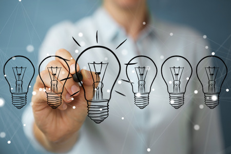 Businesswoman on blurred background drawing a sketch lightbulb with a pen
