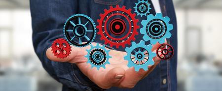 Zakenman op wazig achtergrond bedrijf drijvende versnelling pictogrammen in zijn hand 3D-rendering
