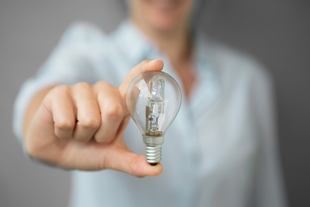 Businesswoman on blurred background holding a lighbulb in her hand