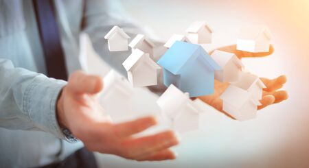 rendered: Businessman on blurred background using 3D rendered small white and blue houses Stock Photo
