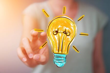 invent: Businesswoman on blurred background holding and touching a lightbulb sketch Stock Photo