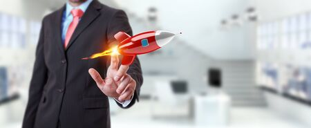 Businessman on blurred background holding and touching a rocket 3D rendering