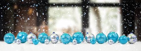 Blue and white christmas baubles lined up on snow background 3D rendering