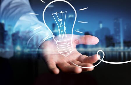 Businessman on blurred background holding a sketch lightbulb Stock Photo