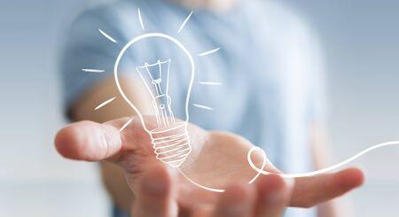 Businessman on blurred background holding a sketch lightbulb Stock Photo