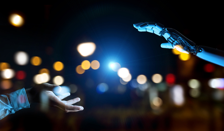 White cyborg hand about to touch human hand on dark background 3D rendering Foto de archivo