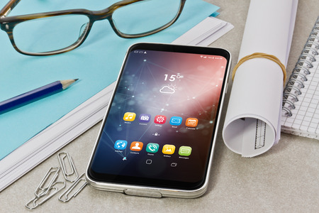 Modern smartphone on a desk in workspace interior