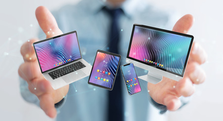 Businessman on blurred background connecting modern smartphone tablet laptop and computer 3D rendering