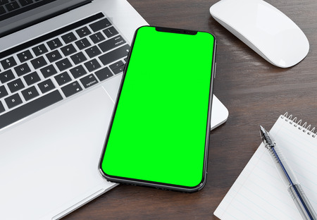 Modern smartphone mockup laying on silver laptop 3d rendering