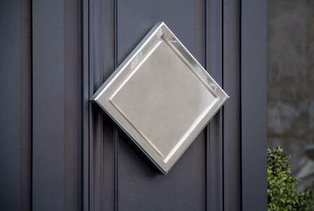 Metallic diamond sign on hotel door mockup. Golden plate on storefront wall in street