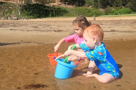 Boy and girl playing in water with buckets and spades on beach photo