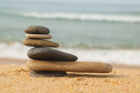 wobble: Pile of smooth stones on sand with waves