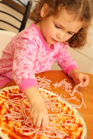 Young girl preparing homemade pizza photo