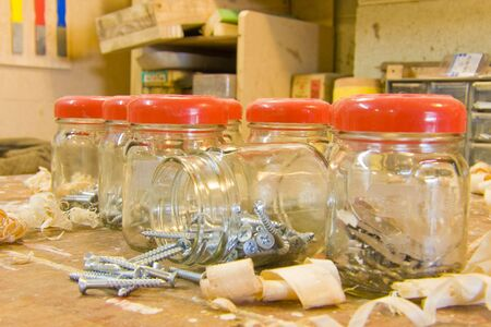 Jars, screws, and woodshavings on workbench Stock Photo - 5060923
