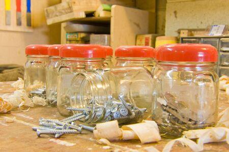 Jars, screws, and woodshavings on workbench Stock Photo - 5060923