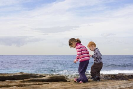 water shoes: Kids stepping in rock pools with ocean background