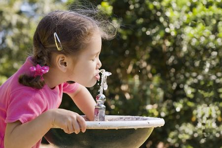 out of water: Young girl drinking from park water fountain.  Out of focus foliage background.  Water motion frozen.