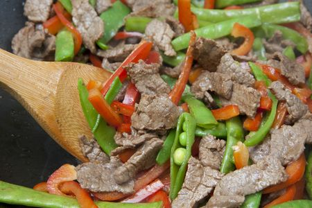 Meat and Vegetable stir-fry being cooked in wok photo