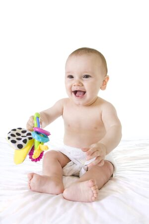 Happy baby laughing and smiling, sitting up with colourful toy on white photo