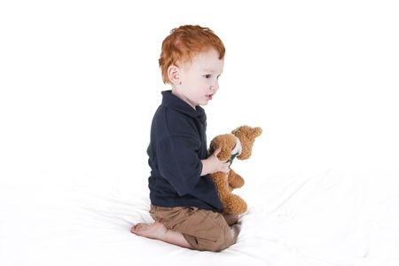 Young boy holding teddy bear and looking intently camera right. photo