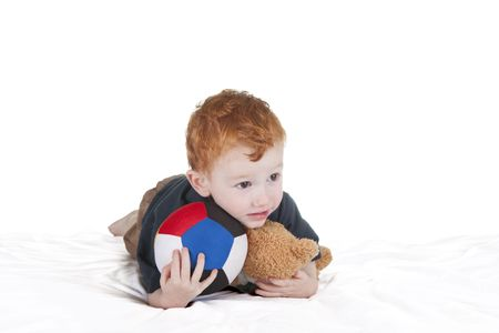Young boy with ball and teddy laying down. photo